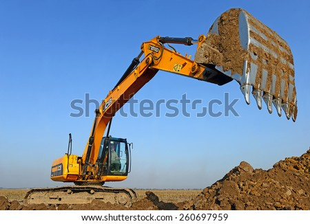 Kalush, Ukraine â?? October 14: Modern JCB excavator on the highway pipeline performs excavation work in the field near the town Kalush, Western Ukraine October 14, 2014 - stock photo