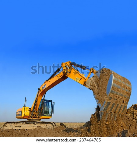 Kalush, Ukraine  October 14: Modern JCB excavator on the highway pipeline performs excavation work in the field near the town Kalush, Western Ukraine October 14, 2014 - stock photo
