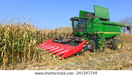 Kalush, Ukraine � OCTOBER 14: Modern John Deere combine harvesting corn  in the field near the town Kalush, Western Ukraine October 14, 2014 - stock photo