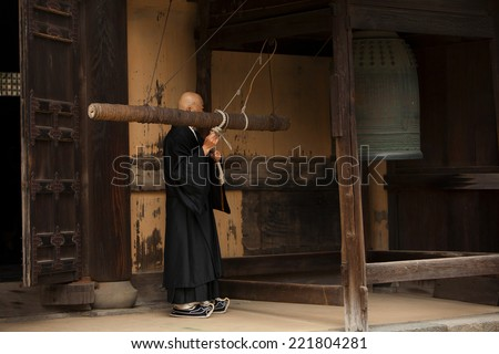 KAMAKURA, JAPAN - MARCH 23, 2009. Buddhist monk rings a bell before a prayer in a monastery in Kamakura.