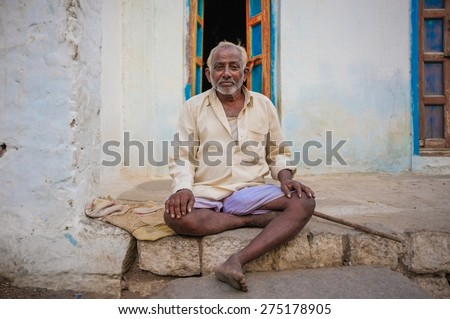 KAMALAPURAM, INDIA - 02 FEBRUARY 2015: Elderly Indian man sitting in front of his home in the old town.