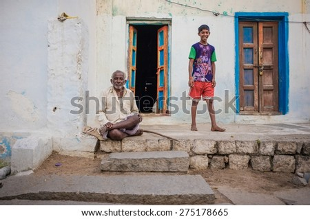 KAMALAPURAM, INDIA - 02 FEBRUARY 2015: Indian father and son outside their home in old town. - stock photo