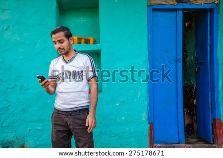KAMALAPURAM, INDIA - 02 FEBRUARY 2015: Indian man looking at this mobile phone outside his home - stock photo