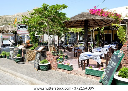 KAMARI, SANTORINI ISLAND, GREECE - MAY 19: The outdoor restaurant near beach on May 19, 2014 in Kamari, Santorini island, Greece. Up to 16 mln tourists is expected to visit Greece in year 2014. - stock photo