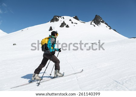 KAMCHATKA, RUSSIA - APRIL 26, 2014: Ski mountaineer climbs on skis on mountain against the background of Mount Camel. Russia, Far East, Kamchatka Peninsula, Avacha pass. - stock photo