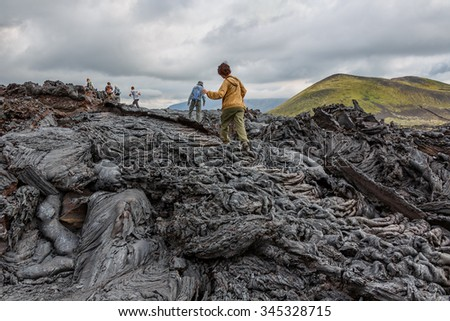 KAMCHATKA, RUSSIA - AUGUST 06, 2013: Tourists go on a route through the active lava flow from a new crater on the slopes of volcanoes Tolbachik, on background volcano Ostry Tolbachik - stock photo