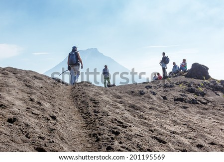 KAMCHATKA, RUSSIA - AUGUST 28, 2013: Tourists had stopped to rest. The active lava flow from a new crater on the slopes of volcanoes Tolbachik, on background volcano Bolshaya Udina