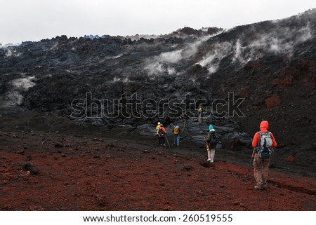 KAMCHATKA, RUSSIA - JULY 27, 2013: Group of tourists hiking on the lava field eruption Tolbachik Volcano on Kamchatka. Russia, Far East, Kamchatka Peninsula, Klyuchevskaya Group of Volcanoes. - stock photo