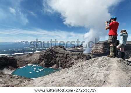 KAMCHATKA, RUSSIA - JULY 21, 2013: Tourists in crater of active Gorely Volcano takes a picture volcanic crater, crater lake and active fumaroles, ejecting steam and gas. Russia, Kamchatka Peninsula. - stock photo