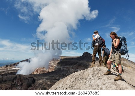 KAMCHATKA, RUSSIA - JULY 21, 2013: Tourists in the crater of active Gorely Volcano watching at the work of the volcano fumaroles. Russia, Far East, Kamchatka Peninsula. - stock photo