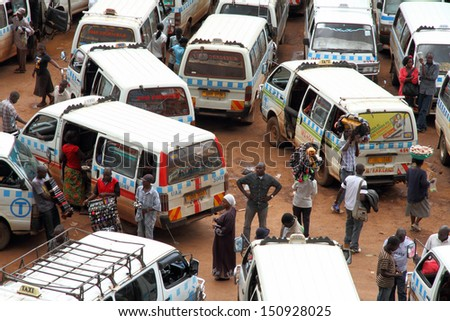 KAMPALA, UGANDA - SEPTEMBER 28, 2012.  Ugandans move about through the taxi park in downtown Kampala, Uganda on September 28,2012. - stock photo