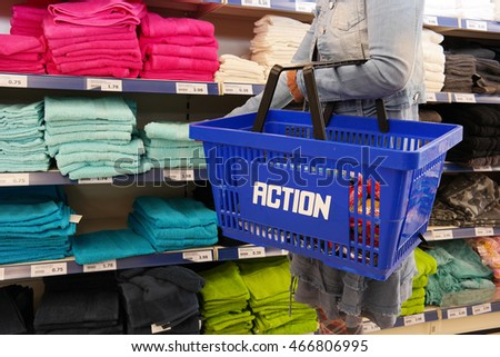 KAMPEN, THE NETHERLANDS - JULY 12, 2016: Shopper with shopping basket in a Action discount superstore. Action is a Dutch discount store-chain. Sells in their variety stores low budget products.