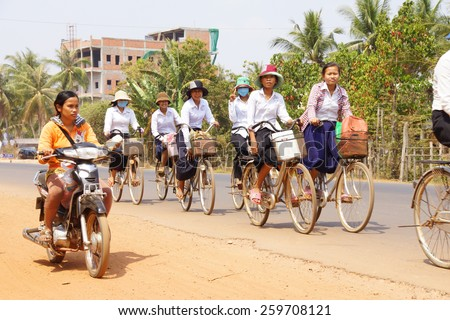 KAMPONG THOM, CAMBODIA - FEB 12, 2015 - Students bicycle home from school along a busy highway,  near Kampong Thom,  Cambodia - stock photo
