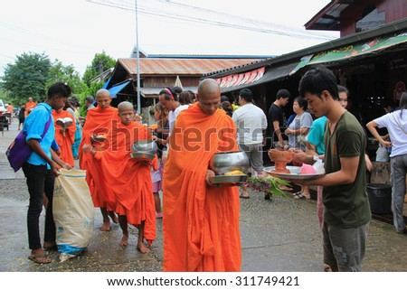 Kanchanaburi, Thailand - July 22, 2013: Buddhists are offering food to monks in the morning in Sangkhlaburi, Kanchanaburi, Thailand. - stock photo