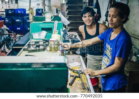KANCHANABURI, THAILAND - JULY 22, 2017: Burmese Male Migrant Workers Cutting or Stitching Leather Shoes with Machine in Footwear Production Line of Factory in Sankhlaburi, Kanchanaburi, Myanmar Border