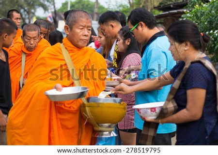 KANCHANABURI, THAILAND -  MAR 25, 2015: Unknown People, give food offerings to a Buddhist monk in Morning, Sangkhlaburi, Kanchanaburi Thailand. As the successor to a long tradition. - stock photo