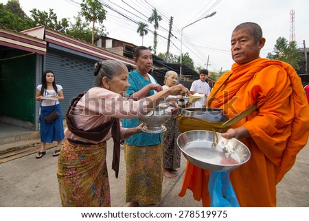 KANCHANABURI, THAILAND -  MAR 25, 2015: Unknown People, give food offerings to a Buddhist monk in Morning, Sangkhlaburi, Kanchanaburi Thailand. As the successor to a long tradition.