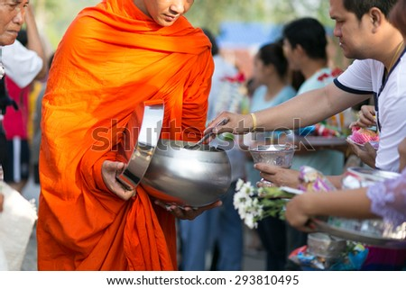 KANCHANABURI THAILAND - MAY 17 : Tourists and locals give alms food to monks during the morning on May 17,2015 in KANCHANABURI,THAILAND - stock photo