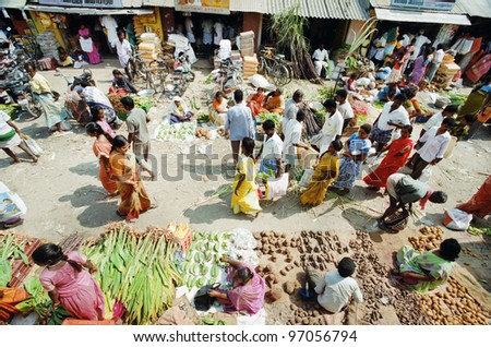 KANCHIPURAM, INDIA - JANUARY 15: Indian people walking around food market at the time of harvest festival Pongal on January 15, 2012 in the ancient indian city Kanchipuram, Tamil Nadu, India. - stock photo