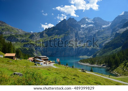 KANDERSTEG, SWITZERLAND - AUGUST 27, 2016: The summer view of Oeschinensee lake (Oeschinen lake) and people going to there for relaxing.