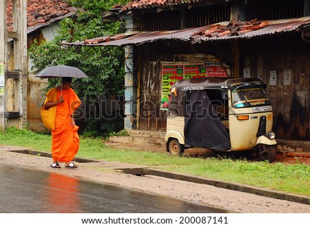 KANDY, SRI LANKA - DECEMBER 6, 2008: Young monk walks down the street to the temple in the rain holding umbrella - stock photo