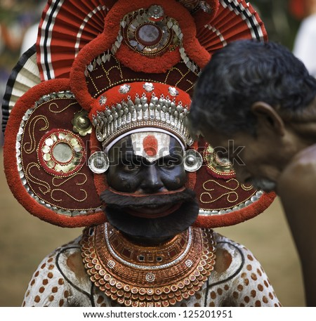 KANNUR, INDIA - DECEMBER 11, 2011: A traditional Theyyam religious performer gives advice to a lay devotee during the annual performance of Theyyam on December 11, 2011 near Kannur, India.