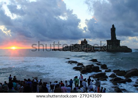 KANYAKUMARI, INDIA - APR 19: Unidentified pilgrims watch sunrise at Triveni Sangam as the sun rises near Vivekananda Rock Memorial and Thiruvalluvar Statue on April 19, 2015, Kanyakumari, India. - stock photo