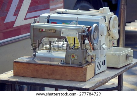 KAOHSIUNG, TAIWAN -- APRIL 5, 2015: An outdoor vendor sells second-hand sewing machines at a local market. - stock photo