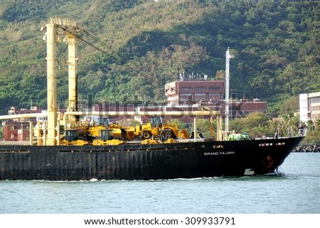 KAOHSIUNG, TAIWAN - AUGUST 12, 2015: The Panamanian freighter Grand Tajima enters Kaohsiung Port with a cargo of construction equipment and excavators.  - stock photo