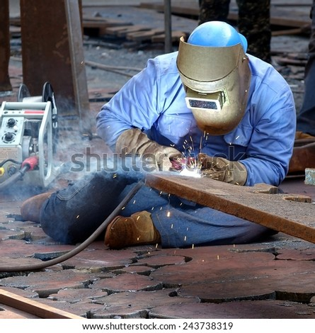 KAOHSIUNG, TAIWAN -- JANUARY 1, 2015: An unidentified welder works on an object for the Kaohsiung Iron and Steel Sculpture Festival. - stock photo