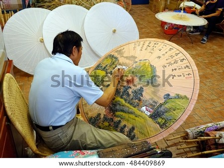 KAOHSIUNG, TAIWAN -- JULY 24, 2016: A male artist paints oil-paper umbrellas, which is a traditional art and craft product by the Chinese Hakka people.