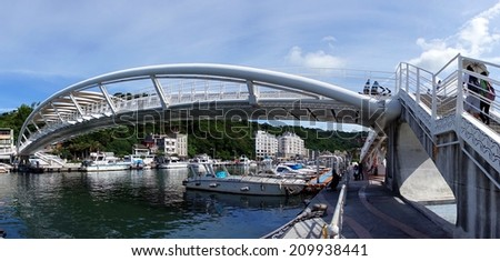 KAOHSIUNG, TAIWAN -- JULY 10, 2014: Panoramic view of a new pedestrian bridge crossing the Gushan marina near to the port of Kaohsiung city. - stock photo