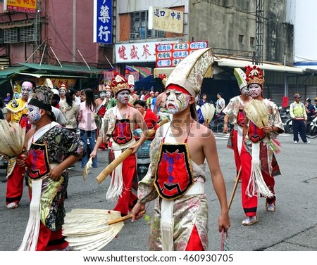 KAOHSIUNG, TAIWAN -- JULY 9, 2016: Young men in traditional costumes and painted facial masks take part in a local temple ceremony.