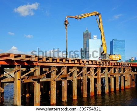 KAOHSIUNG, TAIWAN -- JUNE 14, 2015: An excavator drives a pile into the river bed as construction of a new bridge across the Love River continues. - stock photo