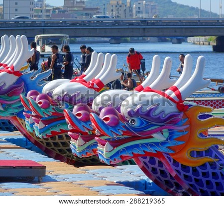 KAOHSIUNG, TAIWAN -- JUNE 14, 2015: Boats with the traditional dragon head sculpture design are prepared for the yearly Dragon Boat Races on the Love River. - stock photo