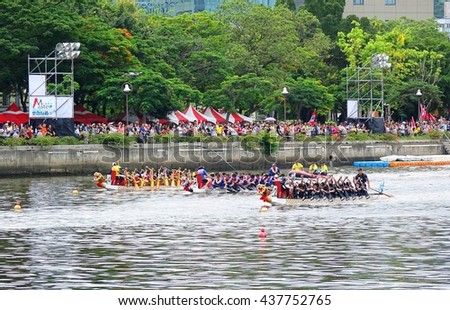 KAOHSIUNG, TAIWAN -- JUNE 9, 2016: Three unidentified teams compete in boat races on the Love River during Dragon Boat Festival.