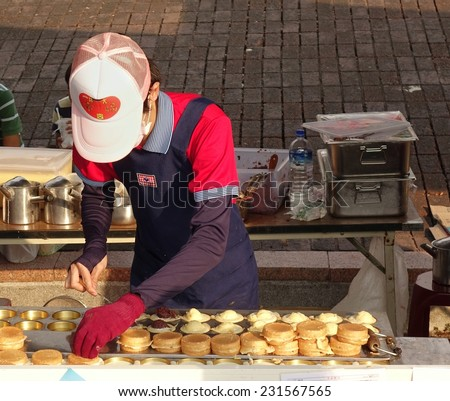 KAOHSIUNG, TAIWAN -- NOVEMBER 8, 2014: An outdoor vendor prepares sweet red bean cakes, a popular Chinese snack. - stock photo