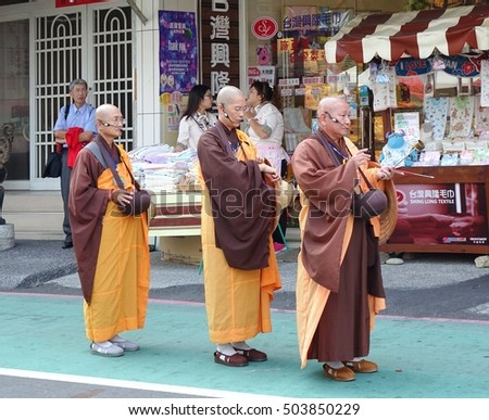 KAOHSIUNG, TAIWAN -- OCTOBER 15, 2016: Three Buddhist monks prepare to chant scriptures during the yearly Wannian Folk Festival.