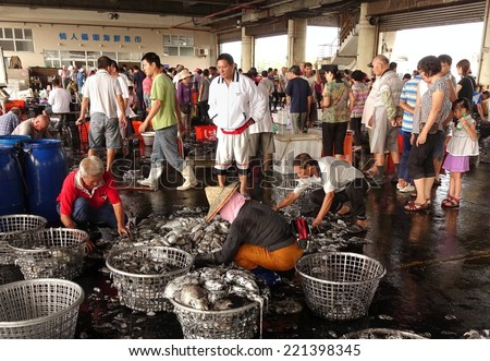KAOHSIUNG, TAIWAN -- SEPTEMBER 28, 2014: Workers at the Sinda fishing port sort fresh squid into baskets to be sold at the daily market. - stock photo
