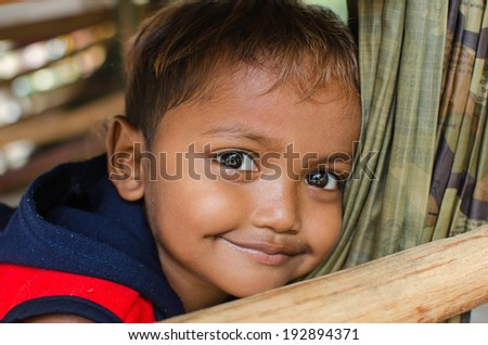 KAP CHOENG,SURIN,THAILAND-MAY 14 : Unidentified khmer kid poses for camera near Thai - Cambodia's border on May 14,2014 at Kap Choeng,Surin,Thailand