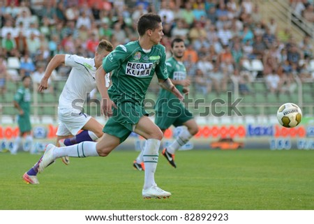 KAPOSVAR, HUNGARY - AUGUST 14: Benjamin Balazs (in green) in action at a Hungarian National Championship soccer game - Kaposvar (green) vs Ujpest (white) on August 14, 2011 in Kaposvar, Hungary.