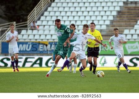 KAPOSVAR, HUNGARY - AUGUST 14: David Hegedus (in green 24) in action at a Hungarian National Championship soccer game - Kaposvar (green) vs Ujpest (white) on August 14, 2011 in Kaposvar, Hungary. - stock photo