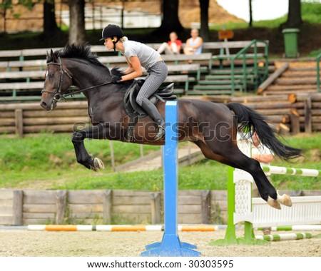 KAPOSVAR, HUNGARY - AUGUST 5: Leila Gyenesei (world champion in pentathlon) jumps with her horse on a training , August 5, 2008 in Kaposvar, Hungary - stock photo