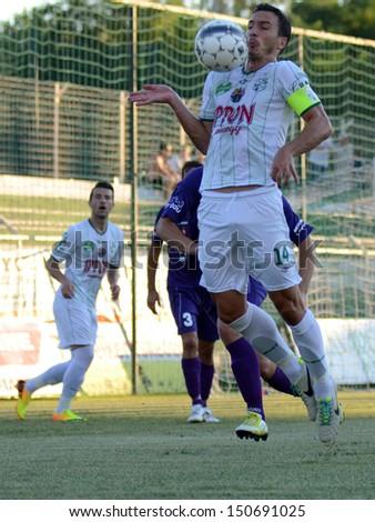 KAPOSVAR, HUNGARY - AUGUST 3: Lorant Olah (white 14) in action at a Hungarian National Championship soccer game - Kaposvar (white) vs Kecskemet (purple) on August 3, 2013 in Kaposvar, Hungary. - stock photo