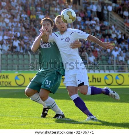 KAPOSVAR, HUNGARY - AUGUST 14: Peter Rajczi (in white) in action at a Hungarian National Championship soccer game - Kaposvar (green) vs Ujpest (white) on August 14, 2011 in Kaposvar, Hungary. - stock photo