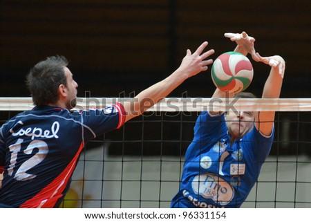 KAPOSVAR, HUNGARY - FEBRUARY 23: Alpar Szabo (R) in action at a Hungarian volleyball National Championship game Kaposvar (blue) vs. Csepel (deep blue), on February 23, 2012 in Kaposvar, Hungary. - stock photo