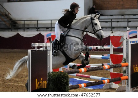 KAPOSVAR, HUNGARY - FEBRUARY 28: An unidentified competitor jumps with her horse on the Winter Jumping Indoor Tournament, February 28, 2010 in Kaposvar, Hungary. - stock photo