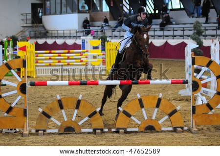 KAPOSVAR, HUNGARY - FEBRUARY 28: An unidentified competitor jumps with his horse on the Winter Jumping Indoor Tournament, February 28, 2010 in Kaposvar, Hungary.
