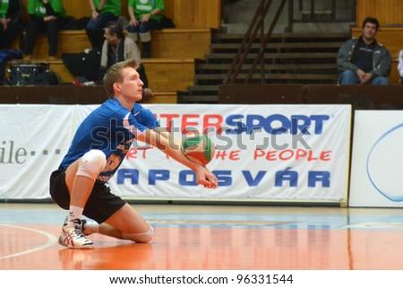 KAPOSVAR, HUNGARY - FEBRUARY 23: Bence Bozoki in action at a Hungarian volleyball National Championship game Kaposvar (blue) vs. Csepel (deep blue), on February 23, 2012 in Kaposvar, Hungary. - stock photo