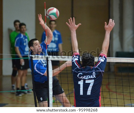 KAPOSVAR, HUNGARY - FEBRUARY 23: Karoly Lesznyik (L) in action at a Hungarian volleyball National Championship game Kaposvar (blue) vs. Csepel ( deep blue), on February 23, 2012 in Kaposvar, Hungary. - stock photo